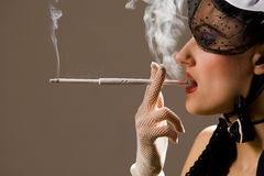 Woman smoking a cigarette Stock Images