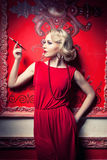 Woman smoking a cigarette in red vintage interior Royalty Free Stock Images
