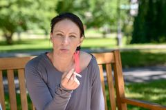 Woman smoking cigarette while sitting on bench Stock Image