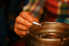 Woman smoking cigarette and using an ashtray, cigarette in an ashtray. Stock Photos