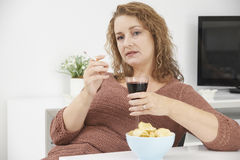 Woman Smoking Cigarette Whilst Drinking Wine And Eating Snacks Royalty Free Stock Image
