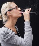 Woman smoking electronic cigarette Stock Images