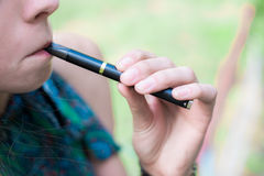 Woman smoking electronic cigarette outdoor Royalty Free Stock Images