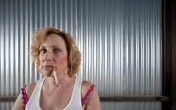Woman smoking in front of corrugated metal Royalty Free Stock Images