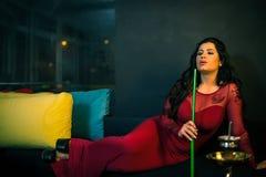 Woman smoking hookah in bar Stock Image