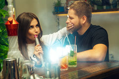 Woman smoking a hookah and closes the mouth hand to the guy. Beautiful young women smoking a hookah and closes the mouth hand to the guy behind the bar Royalty Free Stock Photography