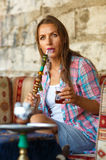 Woman smoking a hookah and drinking tea in a cafe, Istanbul, Tur Royalty Free Stock Image