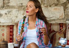 Woman smoking a hookah and drinking tea in a cafe, Istanbul, Tur Royalty Free Stock Images