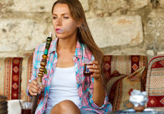 Woman smoking a hookah and drinking tea in a cafe, Istanbul, Tur Royalty Free Stock Photo