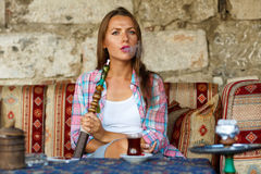 Woman smoking a hookah and drinking tea in a cafe, Istanbul, Tur Stock Photography