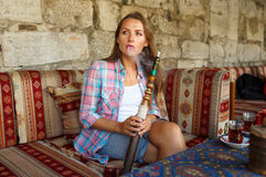 Woman smoking a hookah and drinking tea in a cafe, Istanbul, Tur Royalty Free Stock Photography