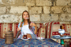 Woman smoking a hookah and drinking tea in a cafe, Istanbul, Tur Stock Image