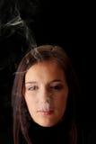 Woman smoking over black Stock Photo