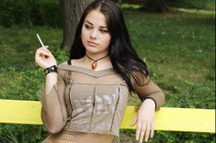 Woman smoking park bench Stock Image