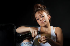 Woman smoking while pouring a drink Royalty Free Stock Photo