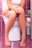 Woman smoking in a toilet room royalty free stock image