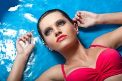 Woman with smoky eyes laying in water Stock Photo