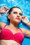 Woman with smoky eyes laying in water Royalty Free Stock Photography