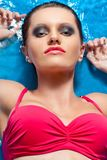 Woman with smoky eyes laying in water Royalty Free Stock Photo