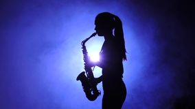 Woman in smoky studio plays on saxophone, silhouette. Slow motion. Woman in smoky studio plays on saxophone, dark silhouette of girl in smoke is visible to waist stock video footage