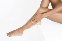 A woman smoothing moisturising lotion onto her legs Stock Images