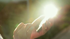 Woman sms texting using app on smart phone at sunset with sun lens flare. Smart phone in female hands. Typing and touching. Close up shot of mobile cell phone stock video footage