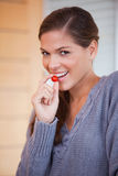 Woman snacking a small tomato Royalty Free Stock Images