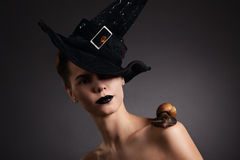 Woman with snail in hat. Fashion. Gothic. Woman with snail on the shoulder in black hat in Gothic Halloween image stock photography