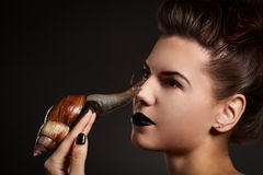 Woman with snail on the nose. Fashion. Gothic. Woman with snail with black eyes and lips in Gothic Halloween image royalty free stock images