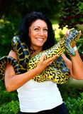 A woman with snake. Young brunet woman with anaconda snake on her shoulder,neck and hands outdoor in a park Stock Image