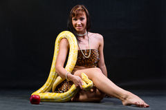 Woman with a snake eating red apple Royalty Free Stock Image