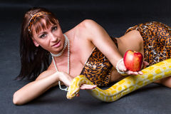 Woman with a snake holding red apple Royalty Free Stock Photo