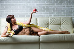 Woman with a snake holding red apple Stock Photos