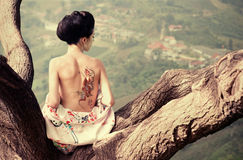 Woman with snake tattoo on her back. Asian style portrait of young woman sitting on the tree branch with snake tattoo on her nacked back stock image