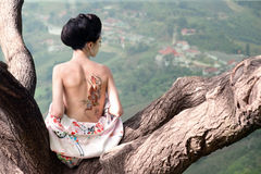 Woman with snake tattoo on her back, original. Asian style portrait of young woman sitting on the tree branch with snake tattoo on her nacked back stock photo