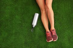 Woman in sneakers with bottle of water sitting on artificial grass, top view. Space for text royalty free stock image