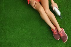 Woman in sneakers with bottle of water sitting on artificial grass, top view. Space for text stock image