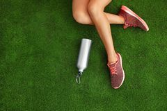 Woman in sneakers with bottle of water sitting on artificial grass, top view. Space for text stock photo
