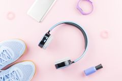 Woman sneakers, headphones, fitness tracker and smartphone on pastel pink background. Sport fashion concept. Flat lay. Top view Stock Images
