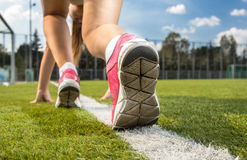 Woman in sneakers standing on white line drawn on grass Royalty Free Stock Image