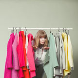 Woman sneaking among clothes in mall or wardrobe. Stock Image