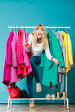 Woman sneaking among clothes in mall or wardrobe. Royalty Free Stock Image