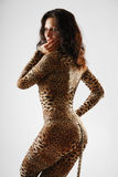 Woman sneaking in dappled catsuit. Sexy woman is sneaking as a cat. She is wearing a leopard catsuit. She is moving sideways and looking at the camera Stock Image