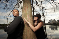 Woman sneaking up on a man. Young woman sneaking up on a man from behind a tree Stock Images