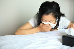 Woman sneeze on bed. Young asian woman catch a cold, sneeze with a running nose on bed Stock Photography