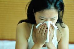 Woman sneeze on bed. Young asian woman sneeze with a running nose on bed Stock Image
