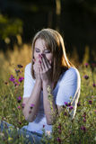 Woman sneezes with allergies. Beautiful young woman in blooming meadow sneezes with allergies Stock Images