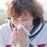 Woman sneezing. Outdoor portrait of an elderly Caucasian brunette woman sneezing into a tissue Stock Photo