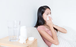 Woman sneezing on bed. Asian young woman Stock Photos