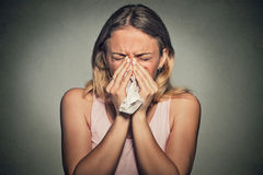 Woman sneezing blowing her runny nose Stock Image